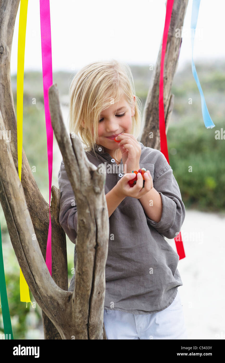 Girl leaning against a tree and eating fruit - Stock Image