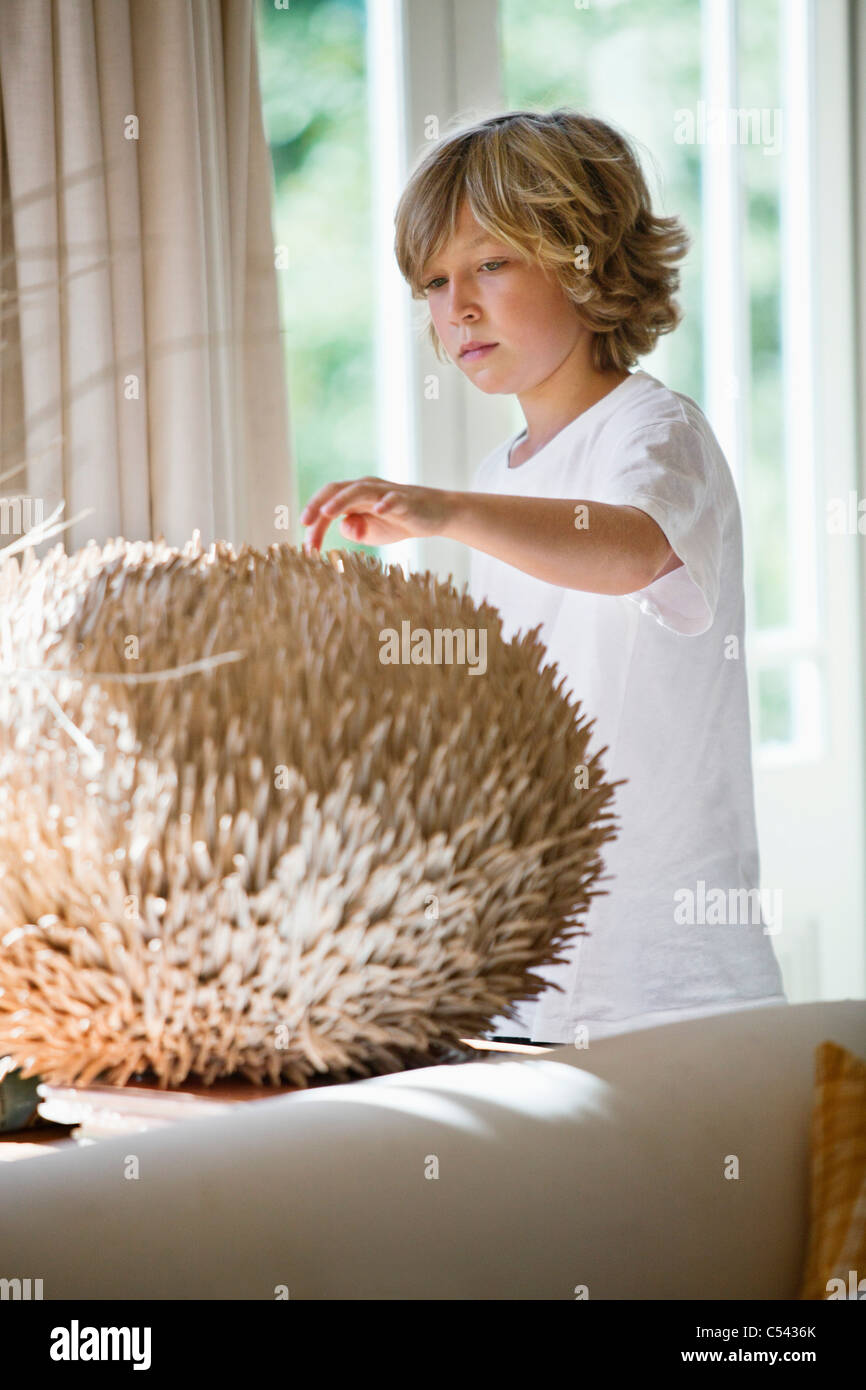 Boy touching a round shape object at home - Stock Image