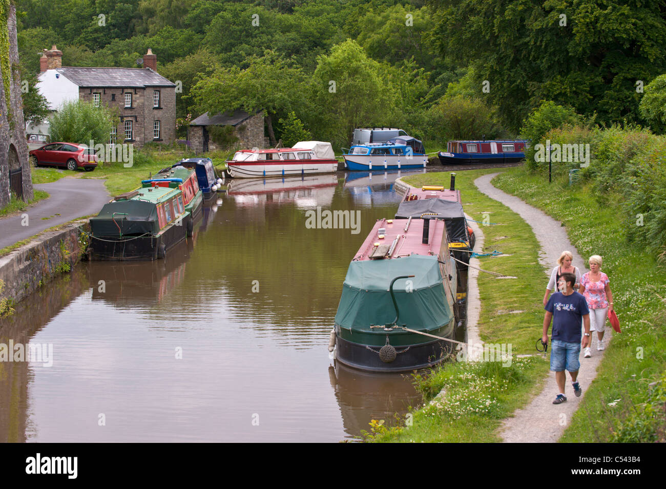 Walkers walking towpath on Monmouthshire and Brecon Canal near village of Llangattock Powys South Wales UK - Stock Image