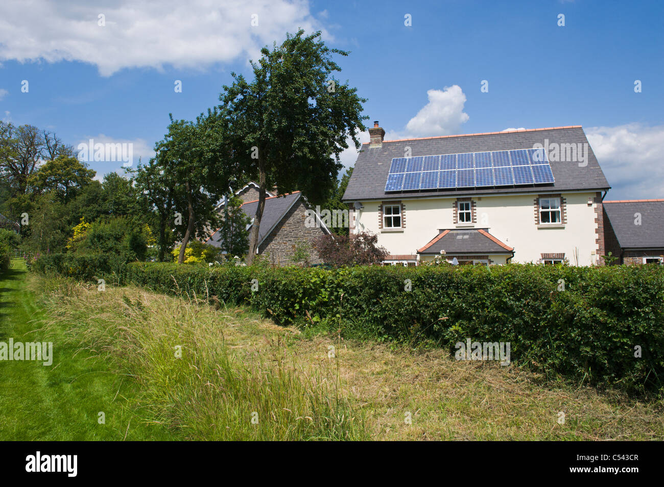 solar panels house UK. Solar panels on roof of detached house in village of Llangattock Powys South Wales UK - Stock Image