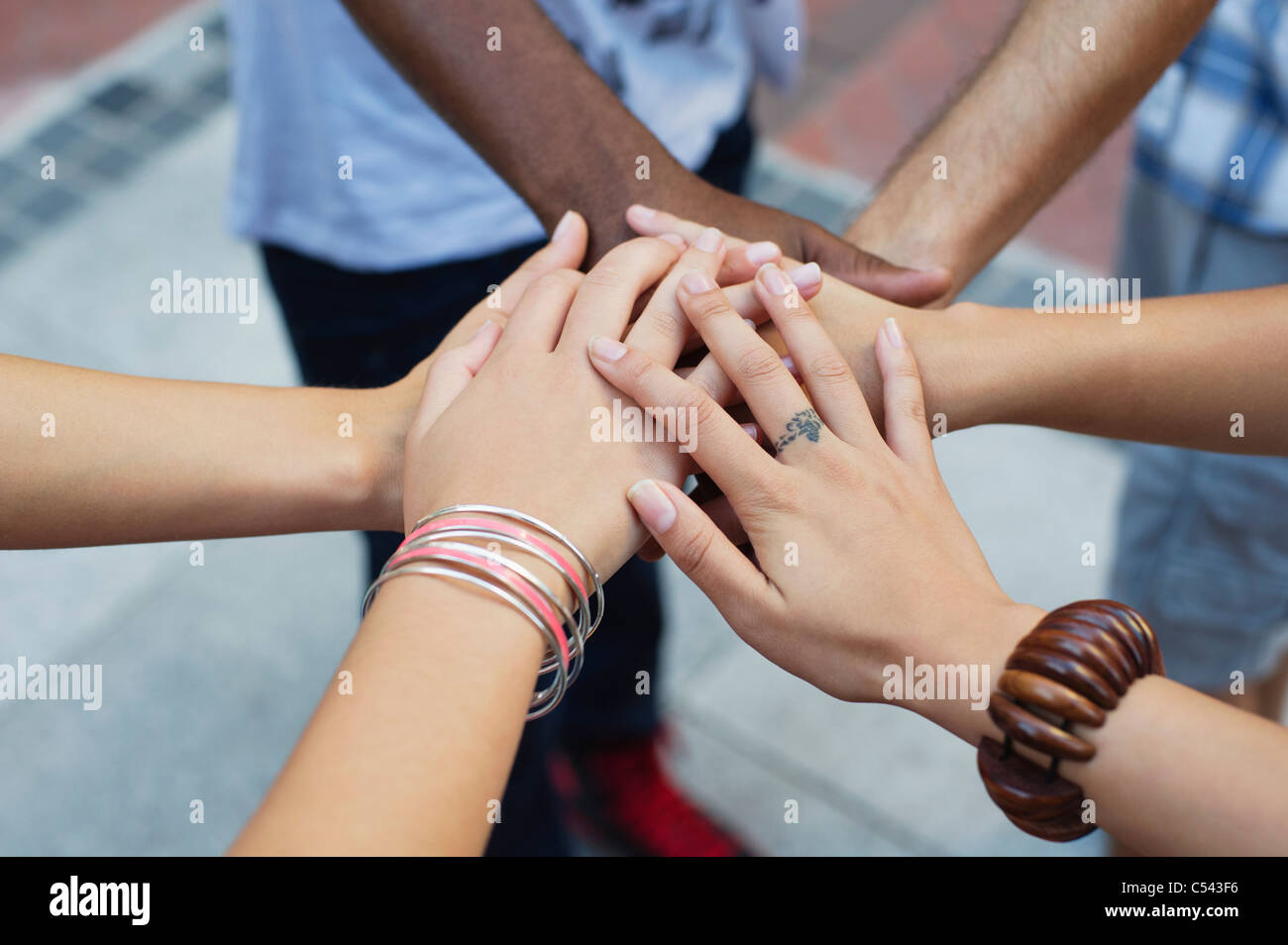 Close-up of human hands stacked upon one another - Stock Image
