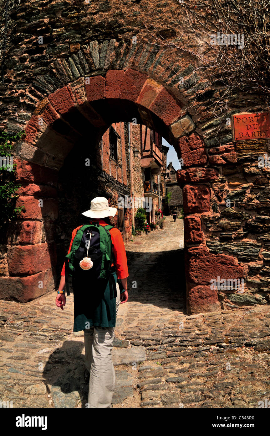 France, St. James Way: Woman passing the medieval village gate 'Porte de Barry' in Conques - Stock Image