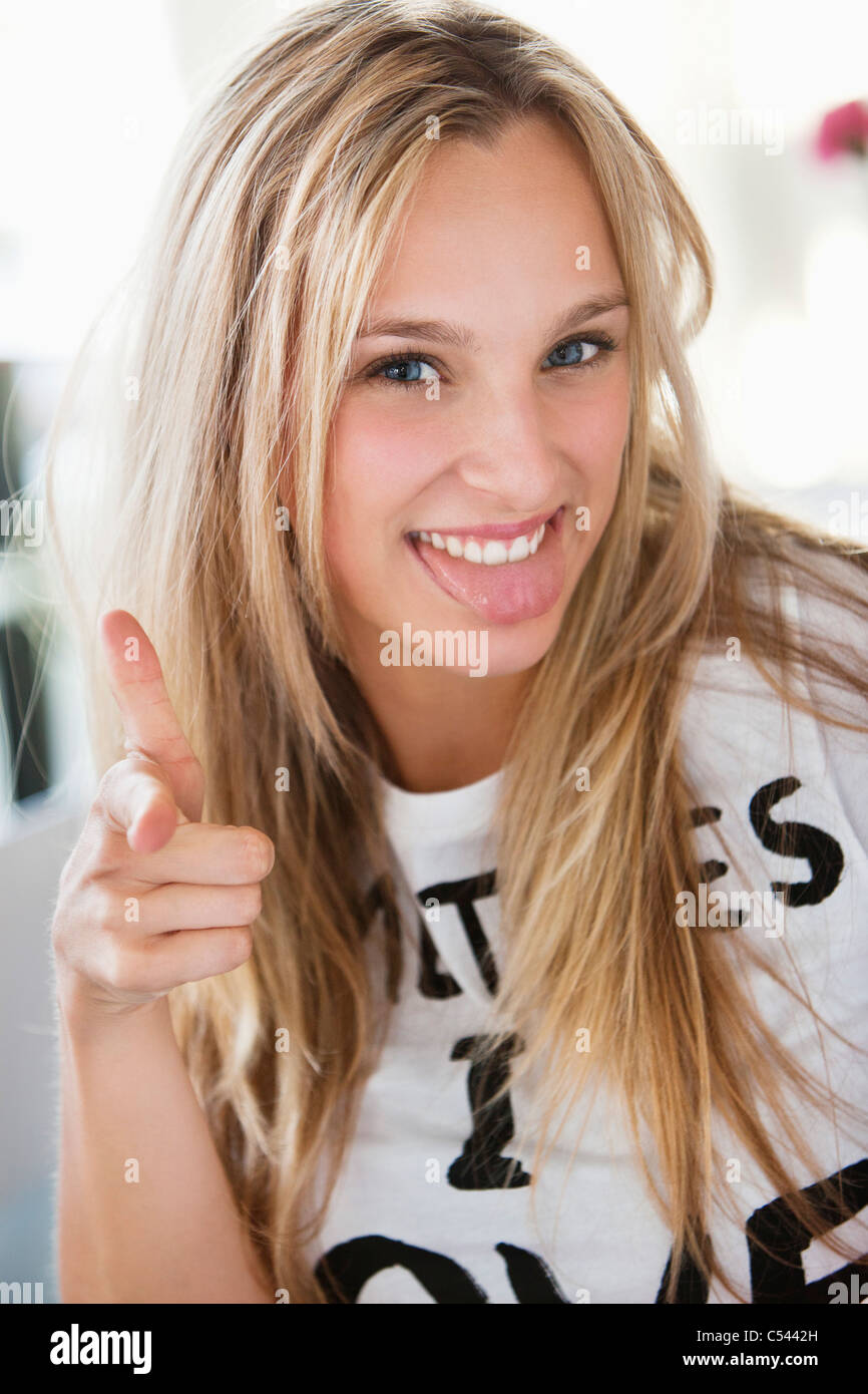 Portrait of a beautiful woman showing gun sign at a cafe - Stock Image