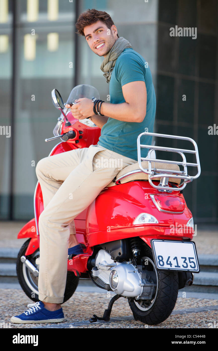 Portrait of young man sitting on a scooter and text messaging - Stock Image