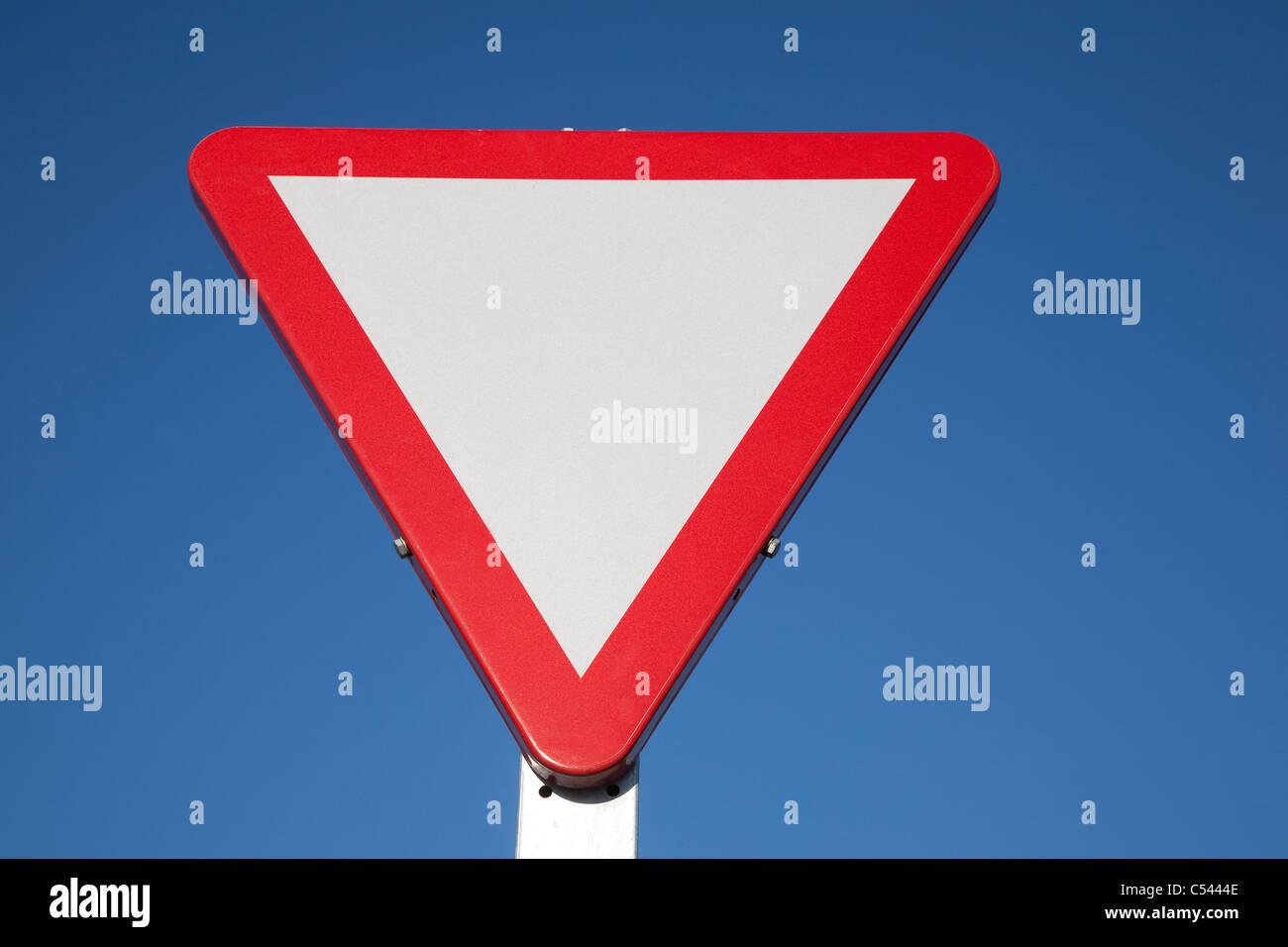 Blank Give Way Sign against Blue Sky Background Stock Photo