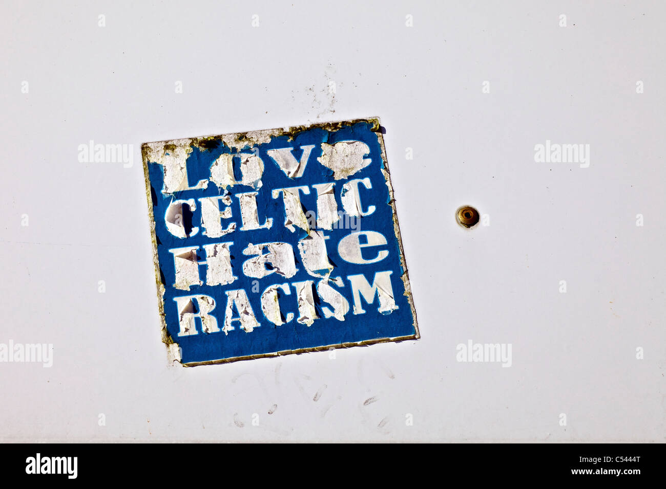 A tattered anti sectarian sticker, Love Celtic Hate Racism - Stock Image