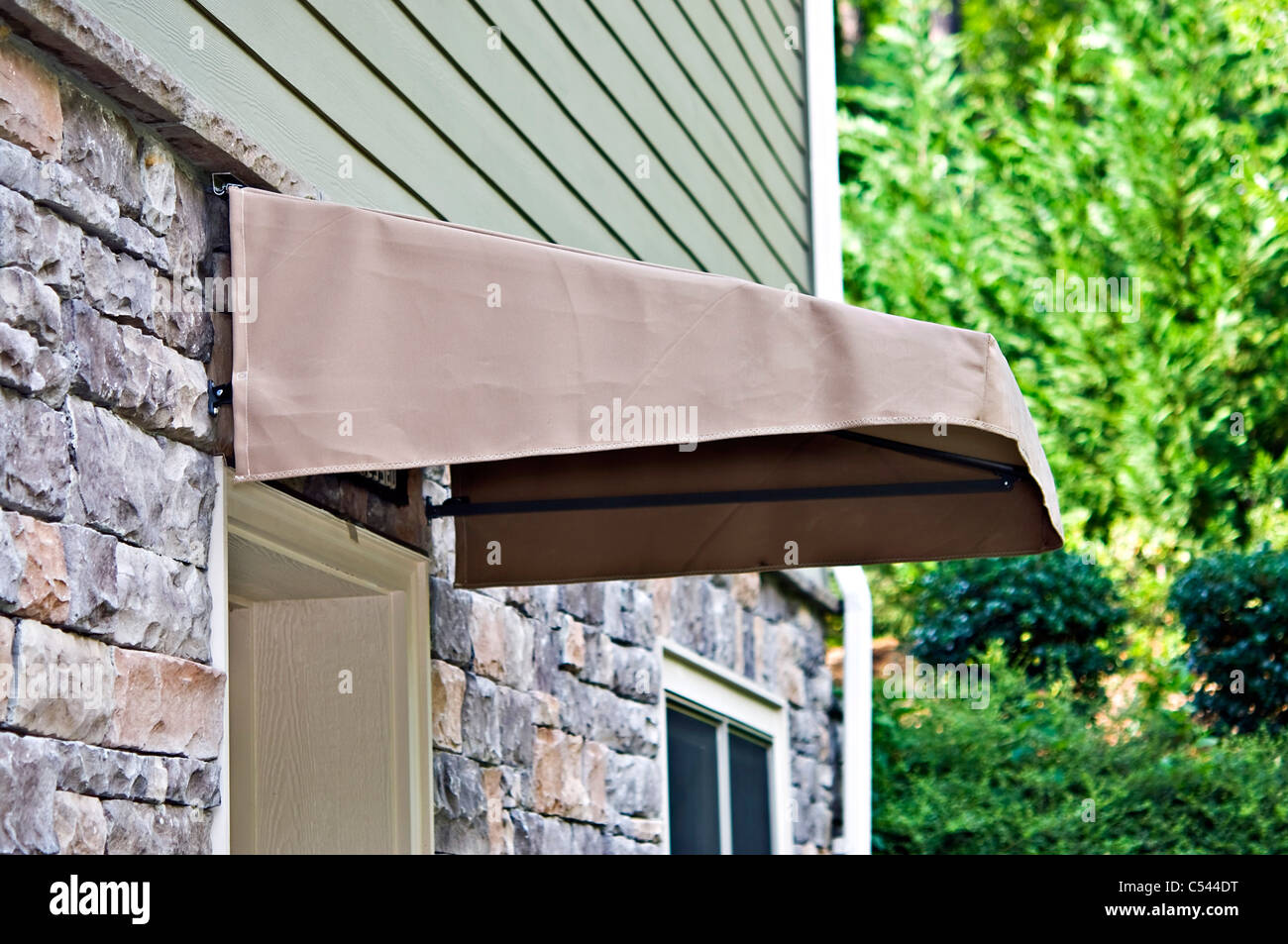 A small canvas awning over an exterior door. - Stock Image