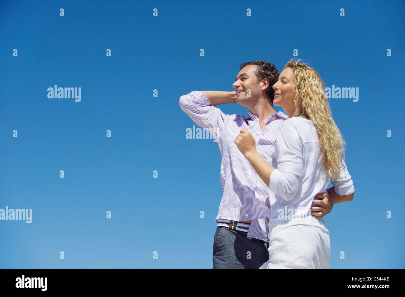 Man standing with his arm around a woman - Stock Image