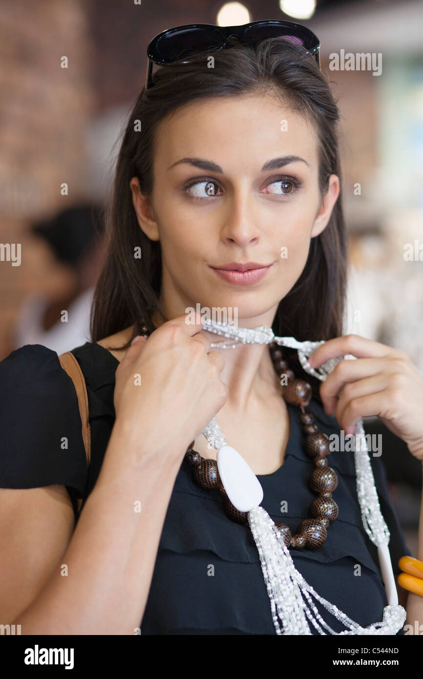 Young woman trying a necklace in a mall - Stock Image