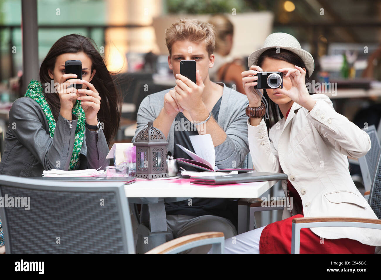 Three young friends using electronic gadgets in a restaurant - Stock Image