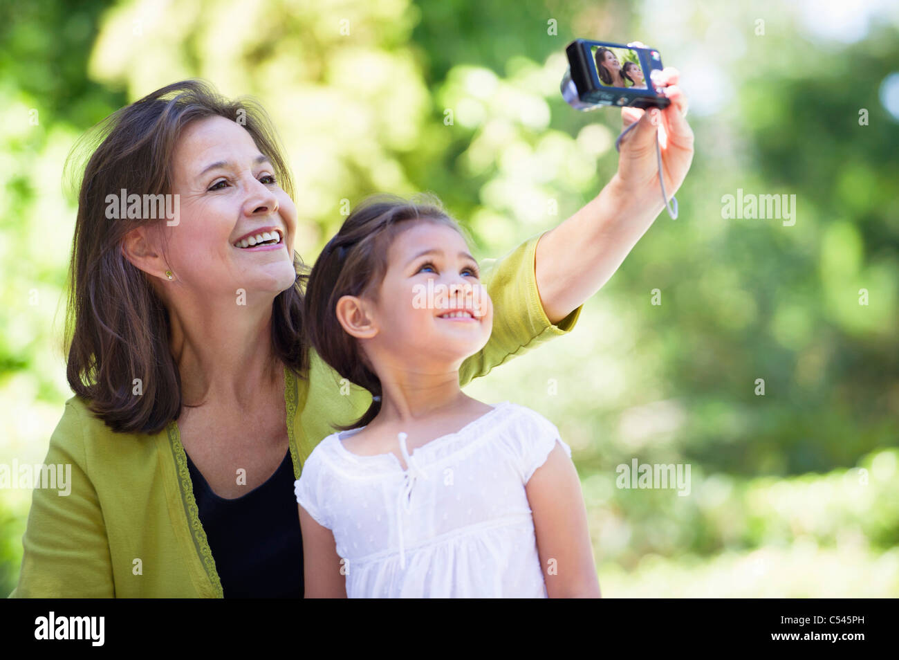 Woman and her granddaughter taking photos of themselves - Stock Image