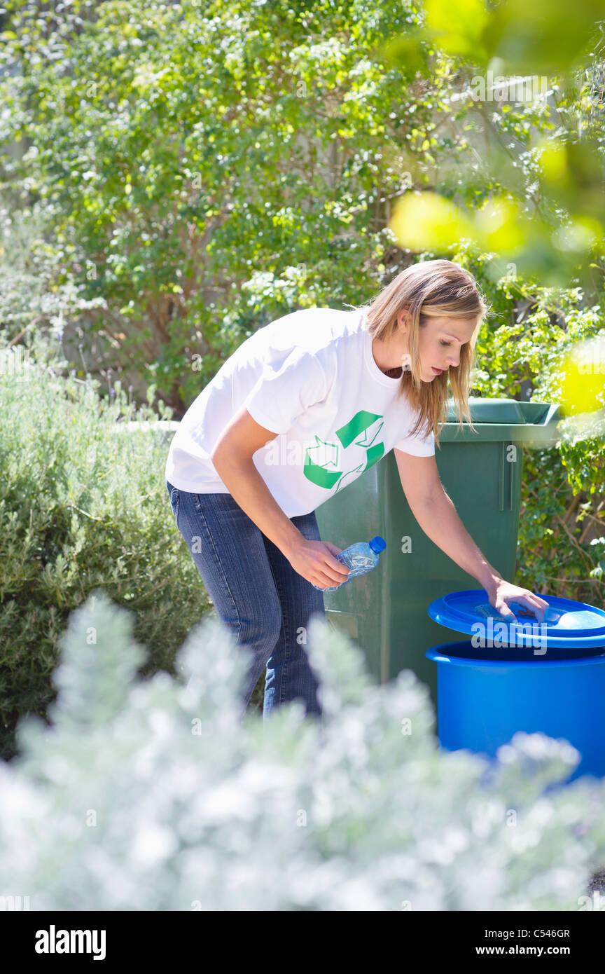 Woman throwing water bottle in garbage bin - Stock Image