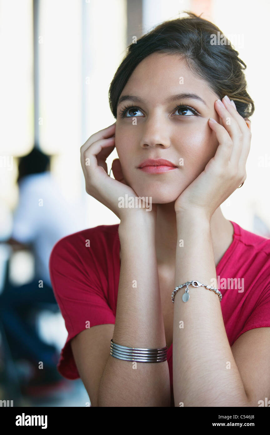 Contemplative woman looking up with head in hands - Stock Image