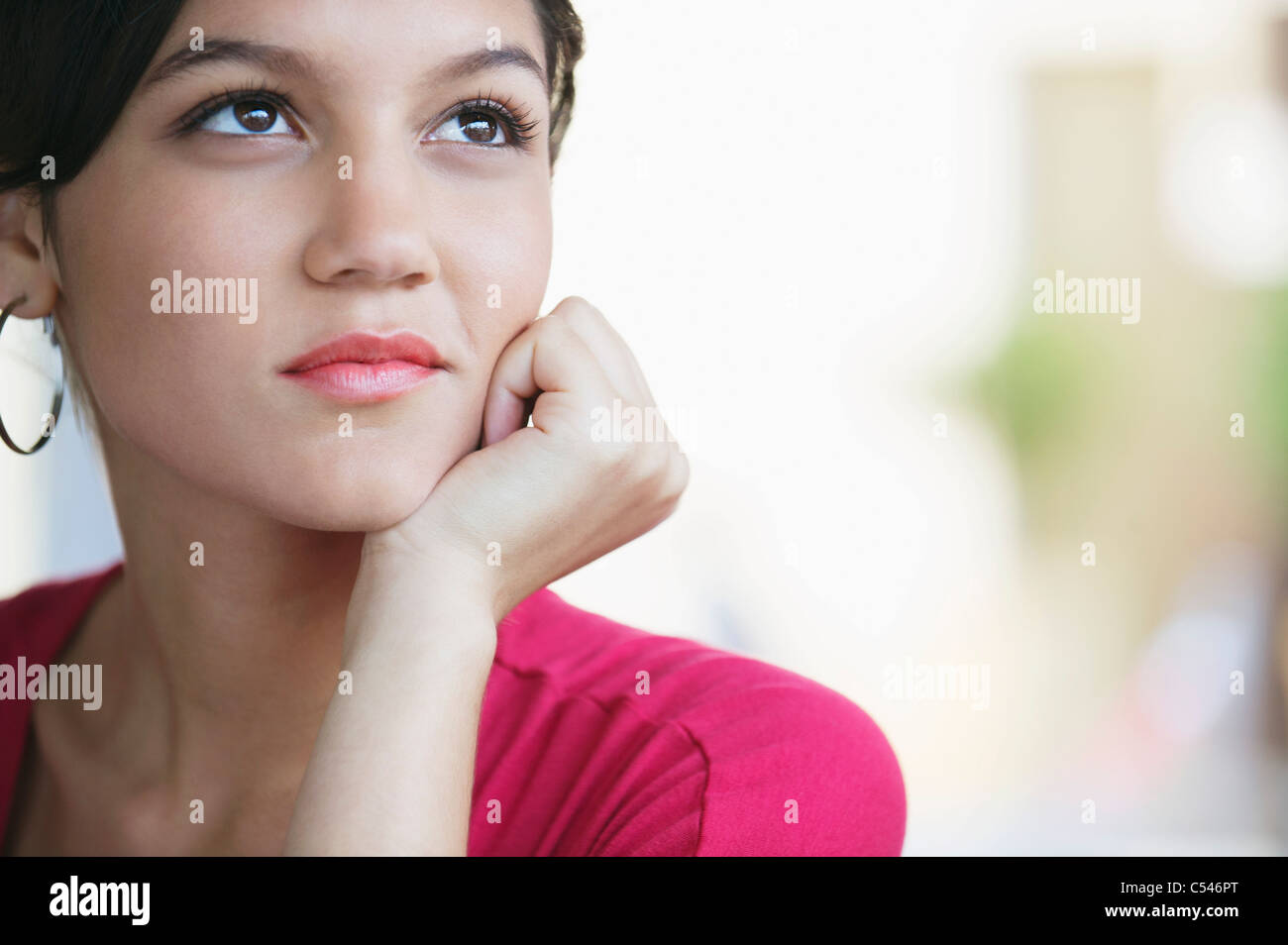 Contemplative woman looking away with hand on chin - Stock Image