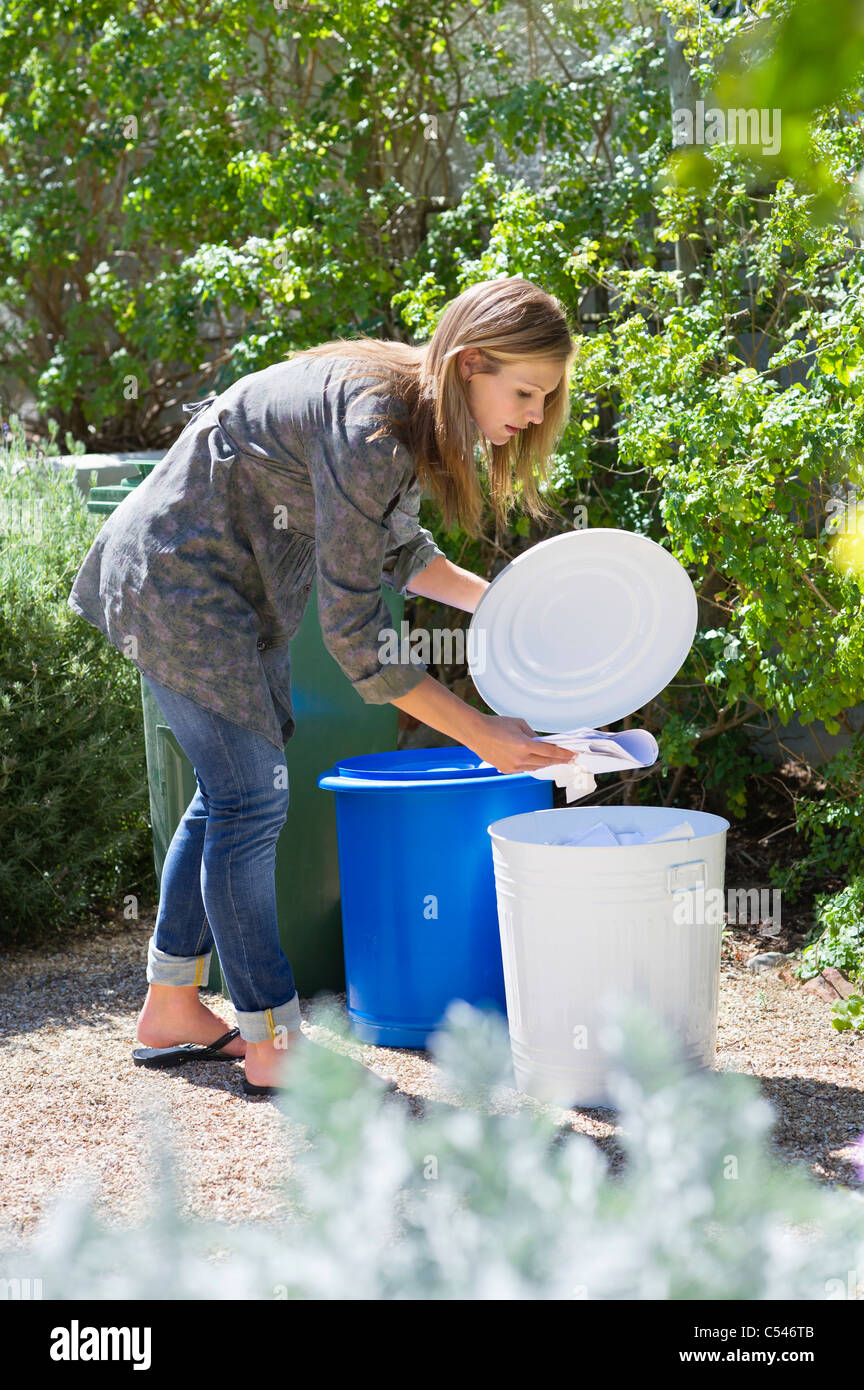 Woman throwing papers in garbage bin - Stock Image