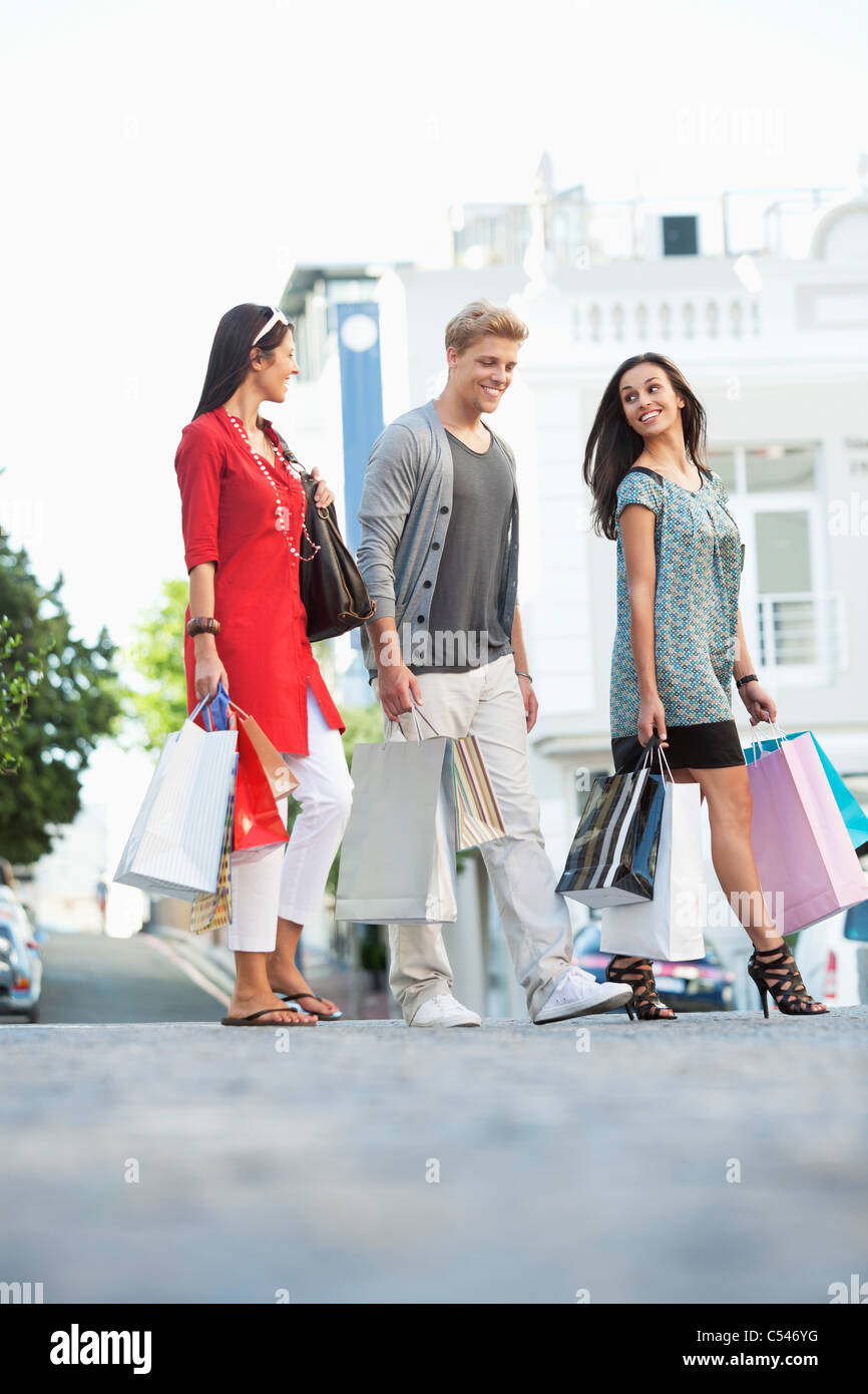 Young man with two women walking with shopping bags - Stock Image