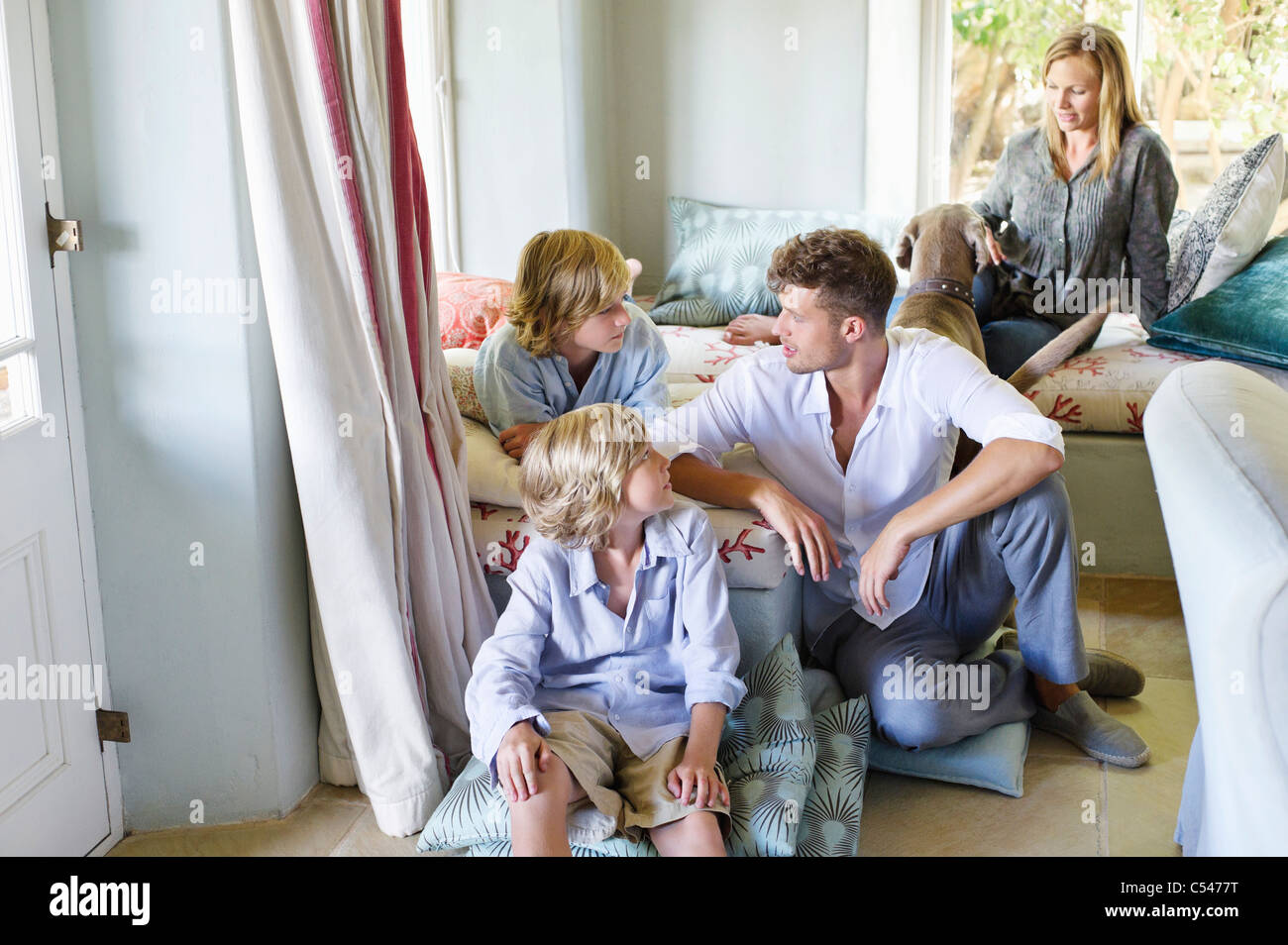 Family sitting together at house - Stock Image
