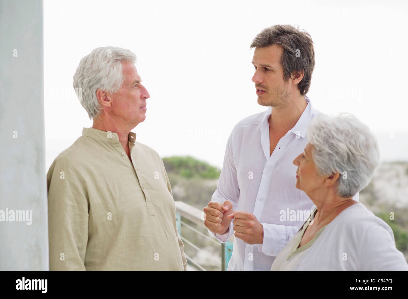 Mid adult man discussing to his parents Stock Photo