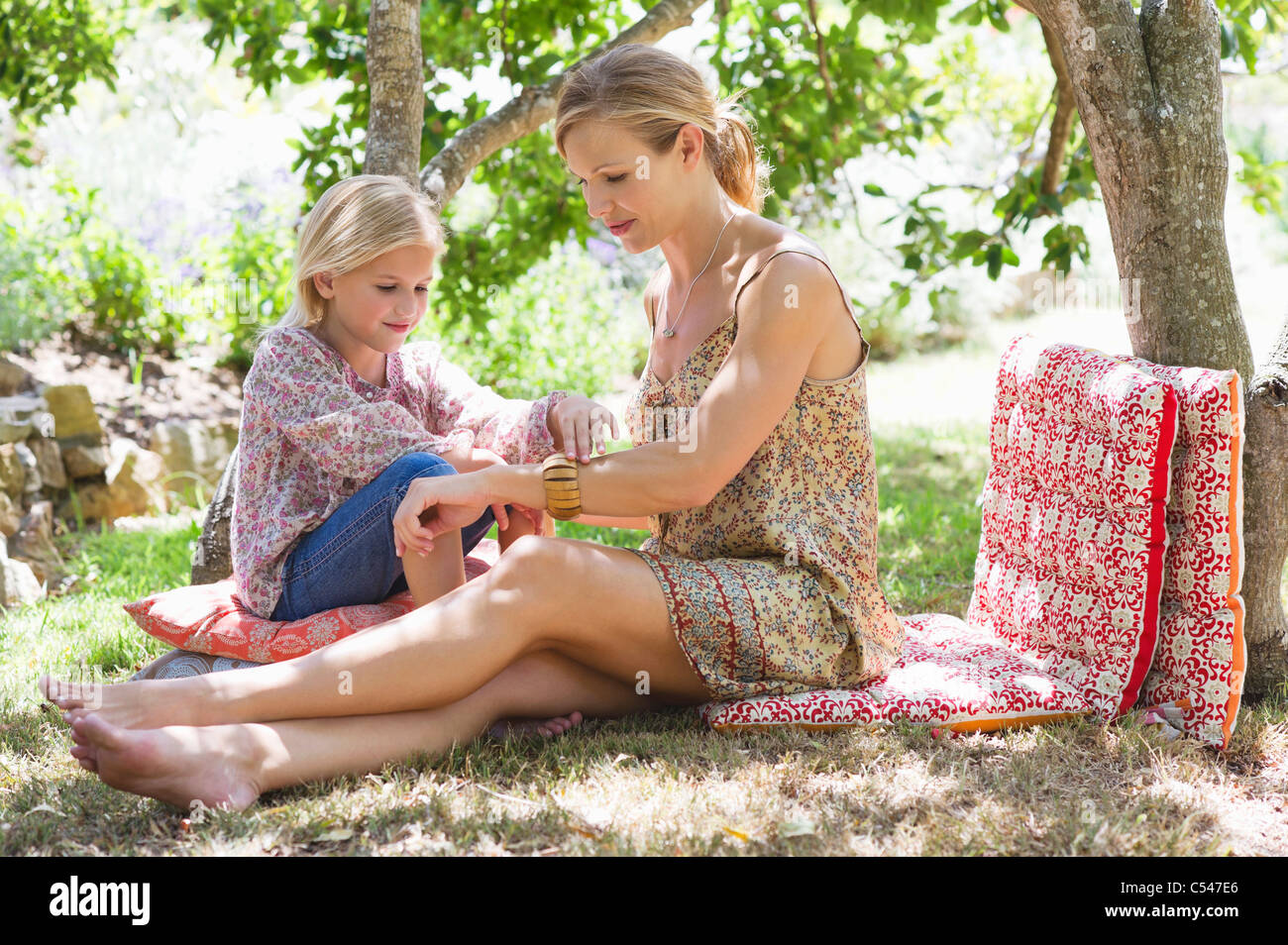 Side profile of mother and a little girl at front or back yard - Stock Image