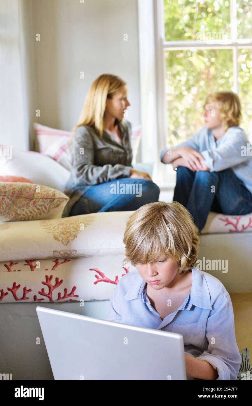 Little boy using laptop with family members talking in the background - Stock Image
