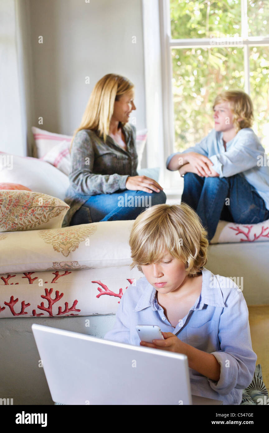Little boy using laptop and mobile phone with family members talking in the background - Stock Image