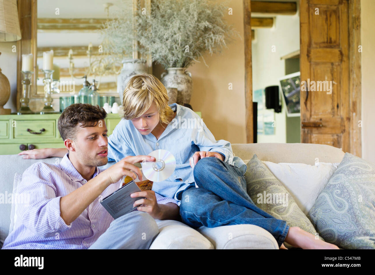 Man and a little boy looking at compact discs - Stock Image