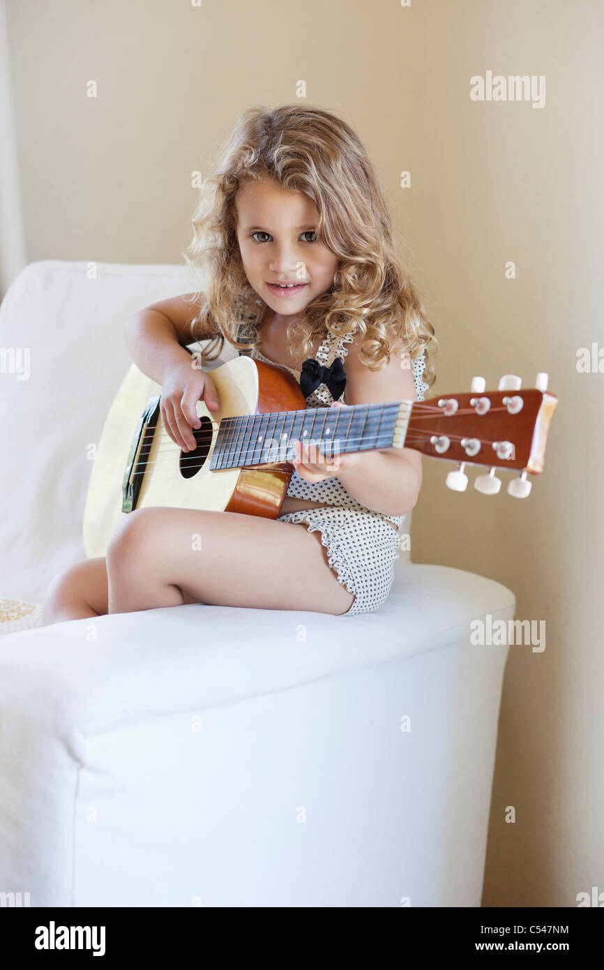 Portrait of a cute little girl playing a guitar - Stock Image
