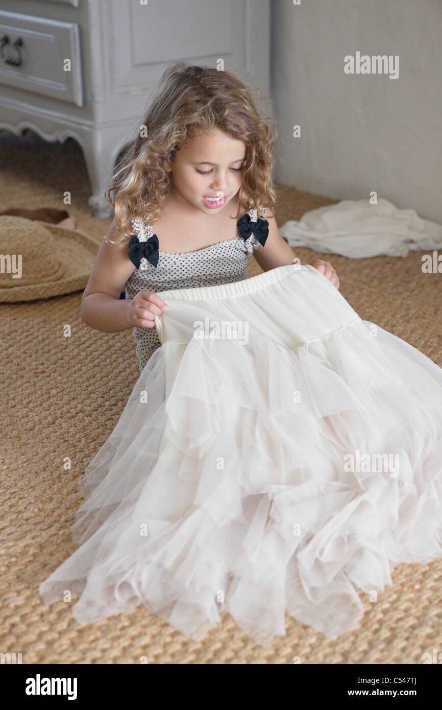 Cute little girl getting dressed like her mother in oversized clothes Stock Photo