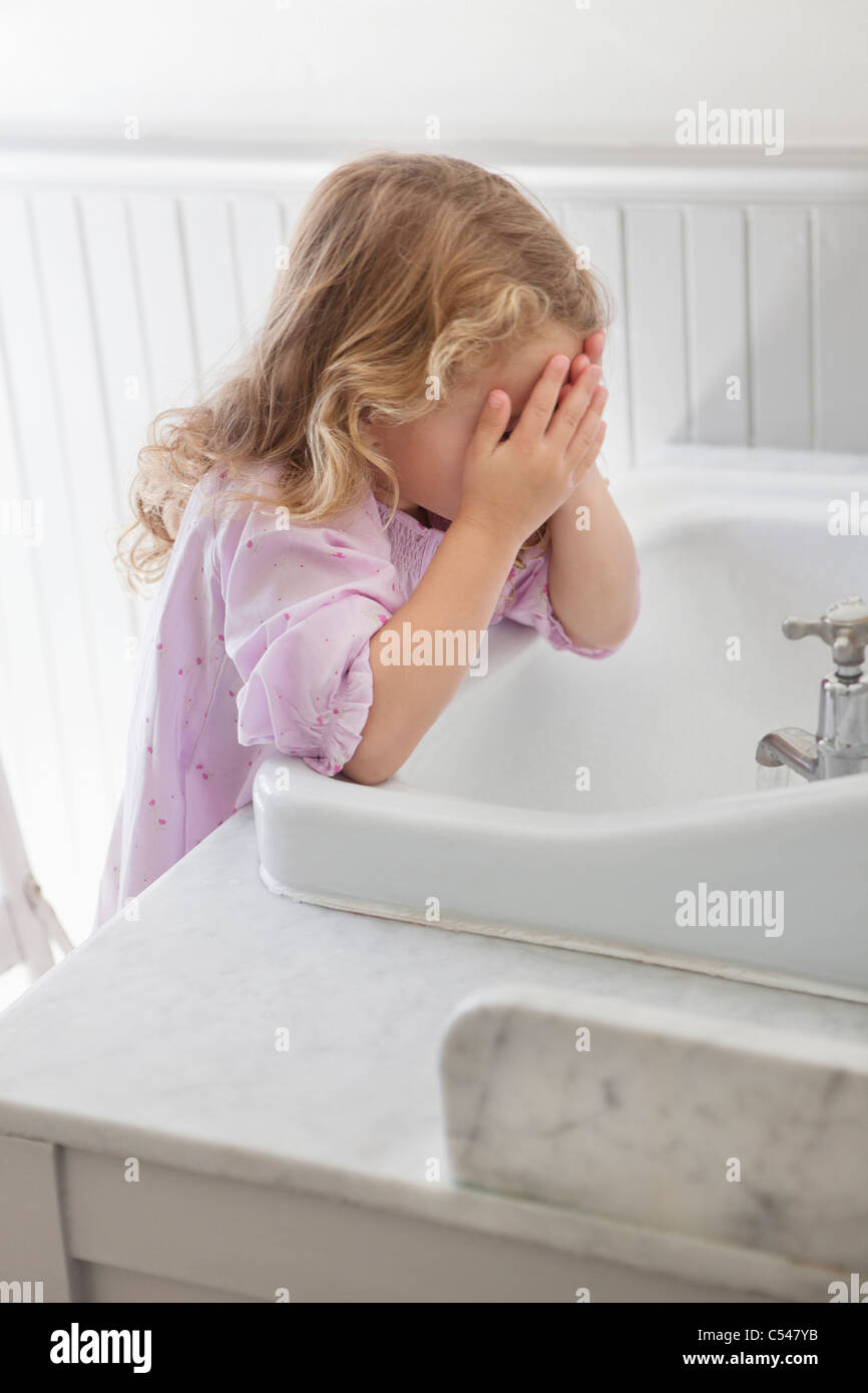 Cute little girl washing face in bathroom sink - Stock Image