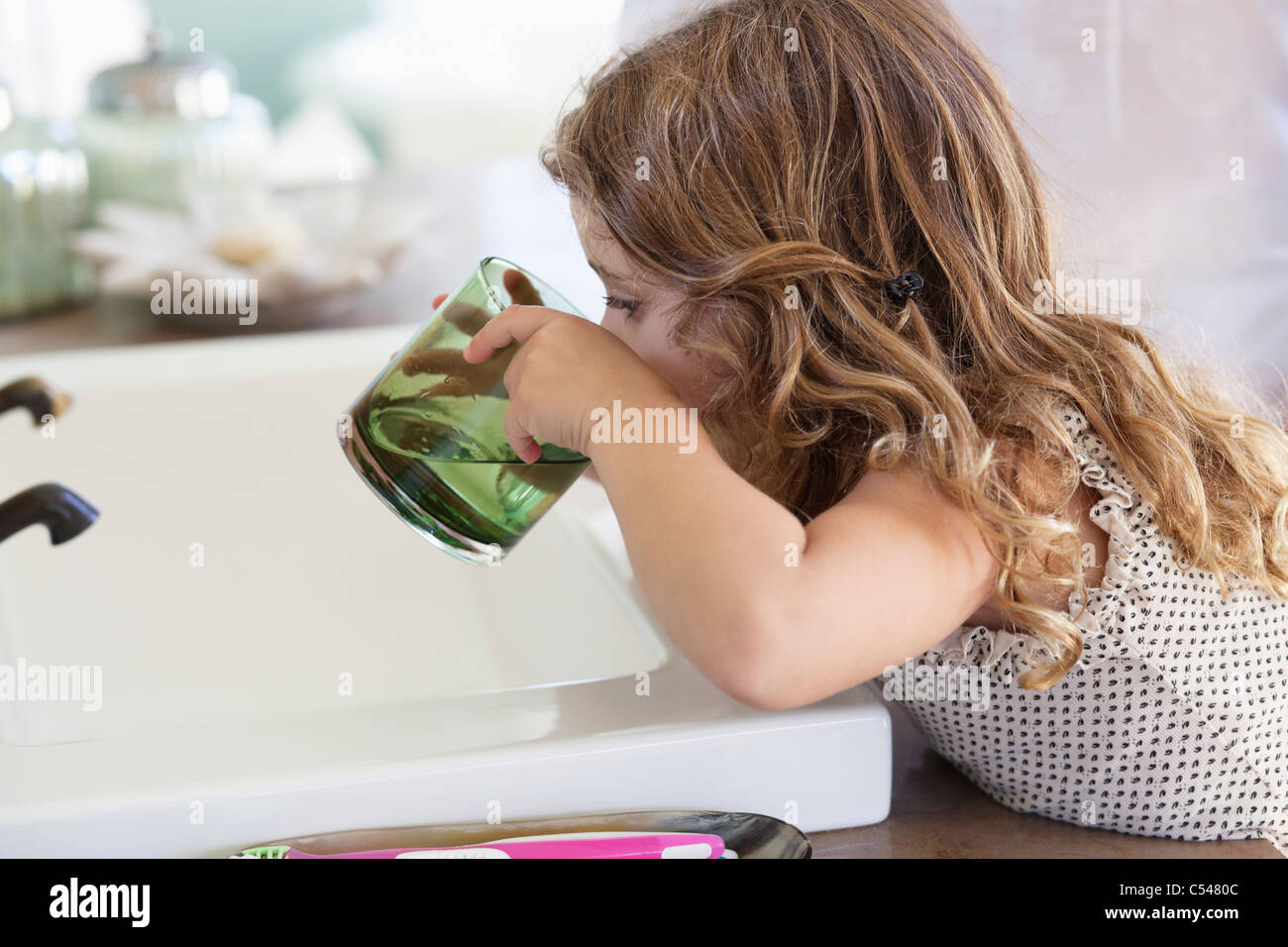 Cute little girl drinking water at bathroom sink - Stock Image