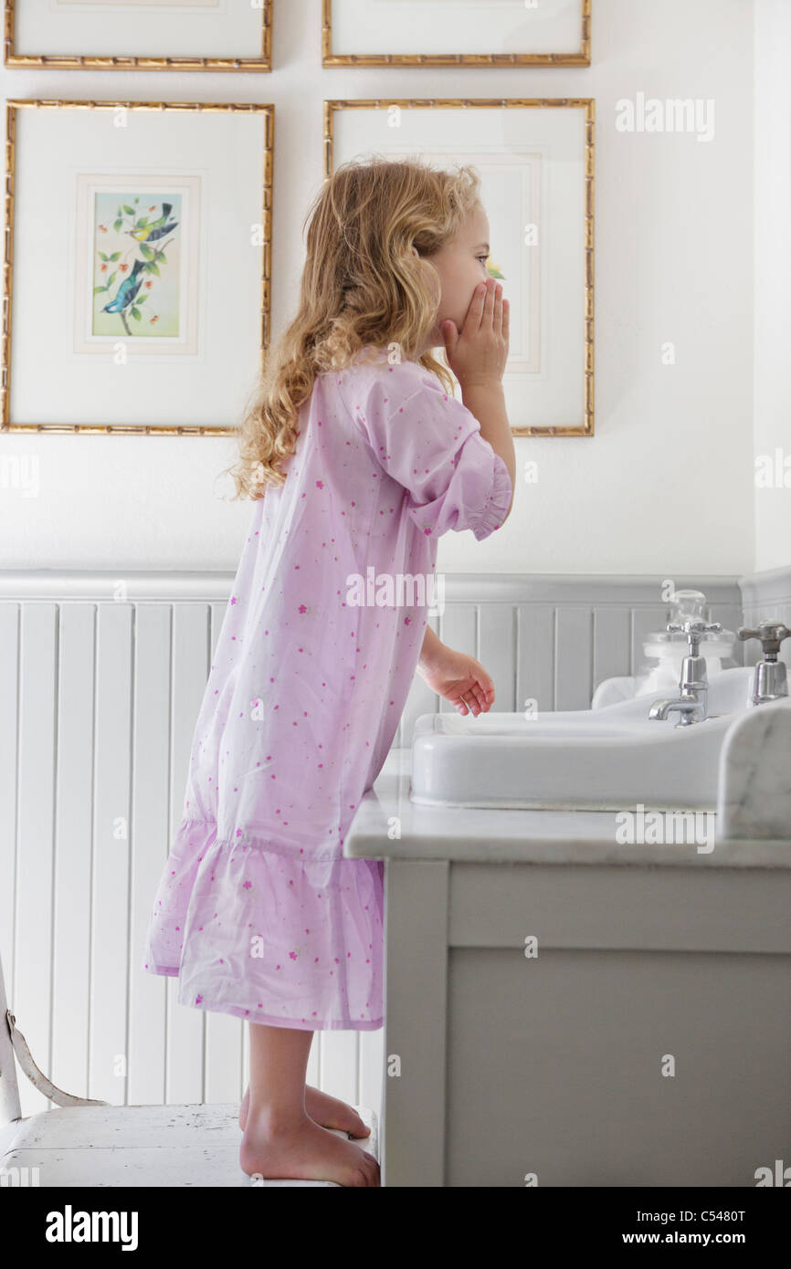 Cute Little Girl Washing Face In A Bathroom   Stock Image