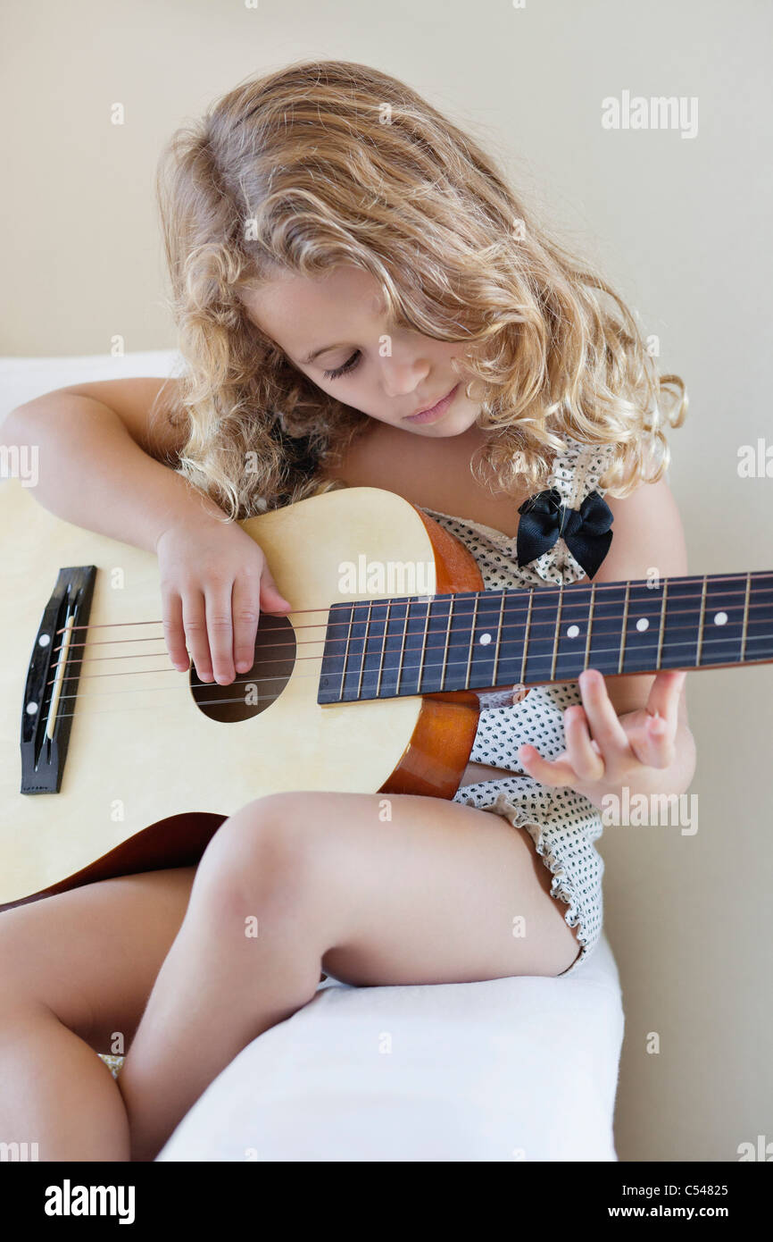 Cute little girl playing a guitar - Stock Image