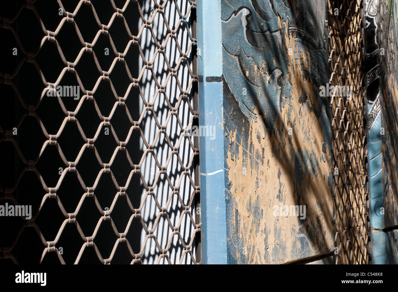 Chicken wire fence, peeling paint and shadows - Stock Image