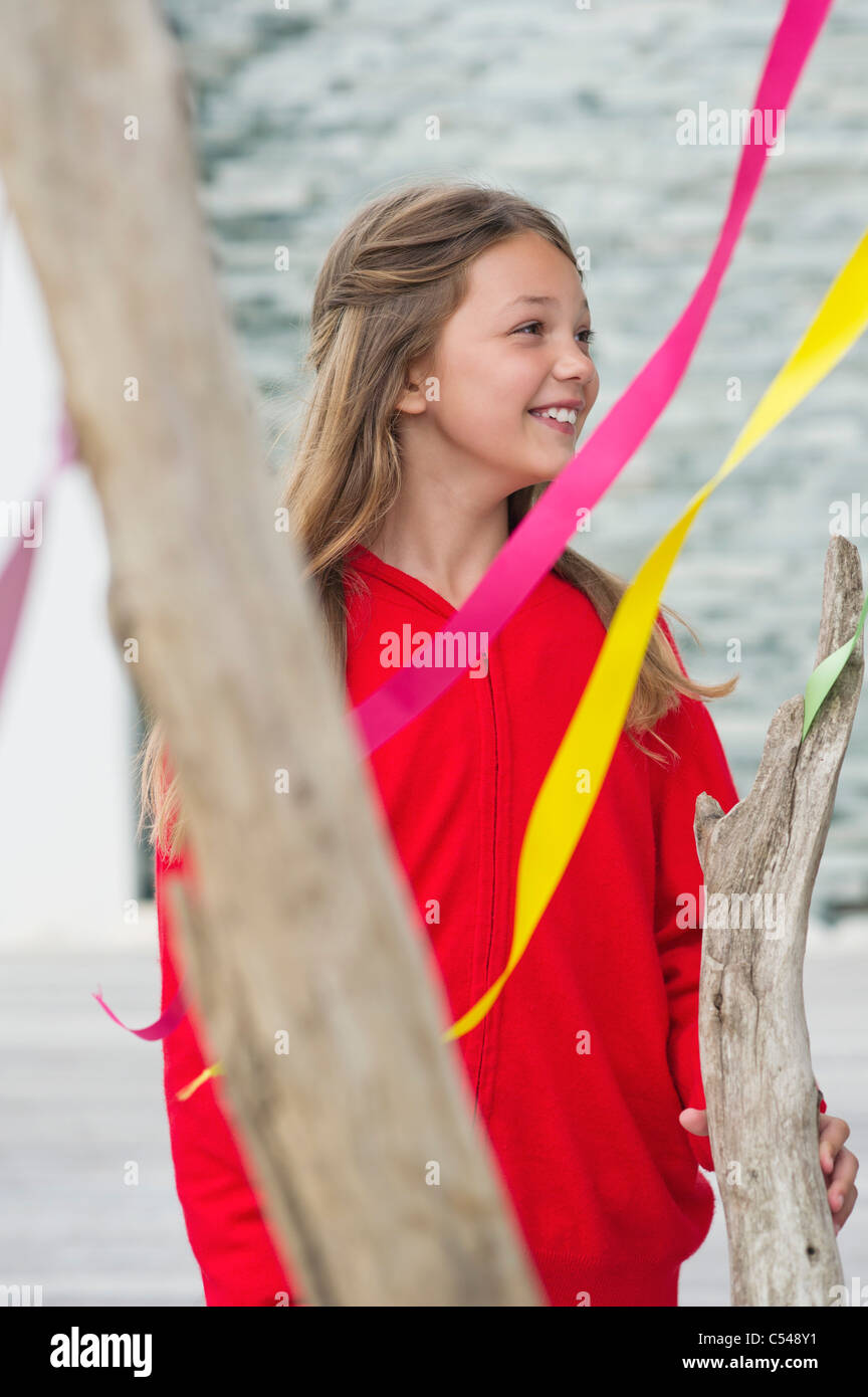 Girl standing near a decorated tree and smiling - Stock Image