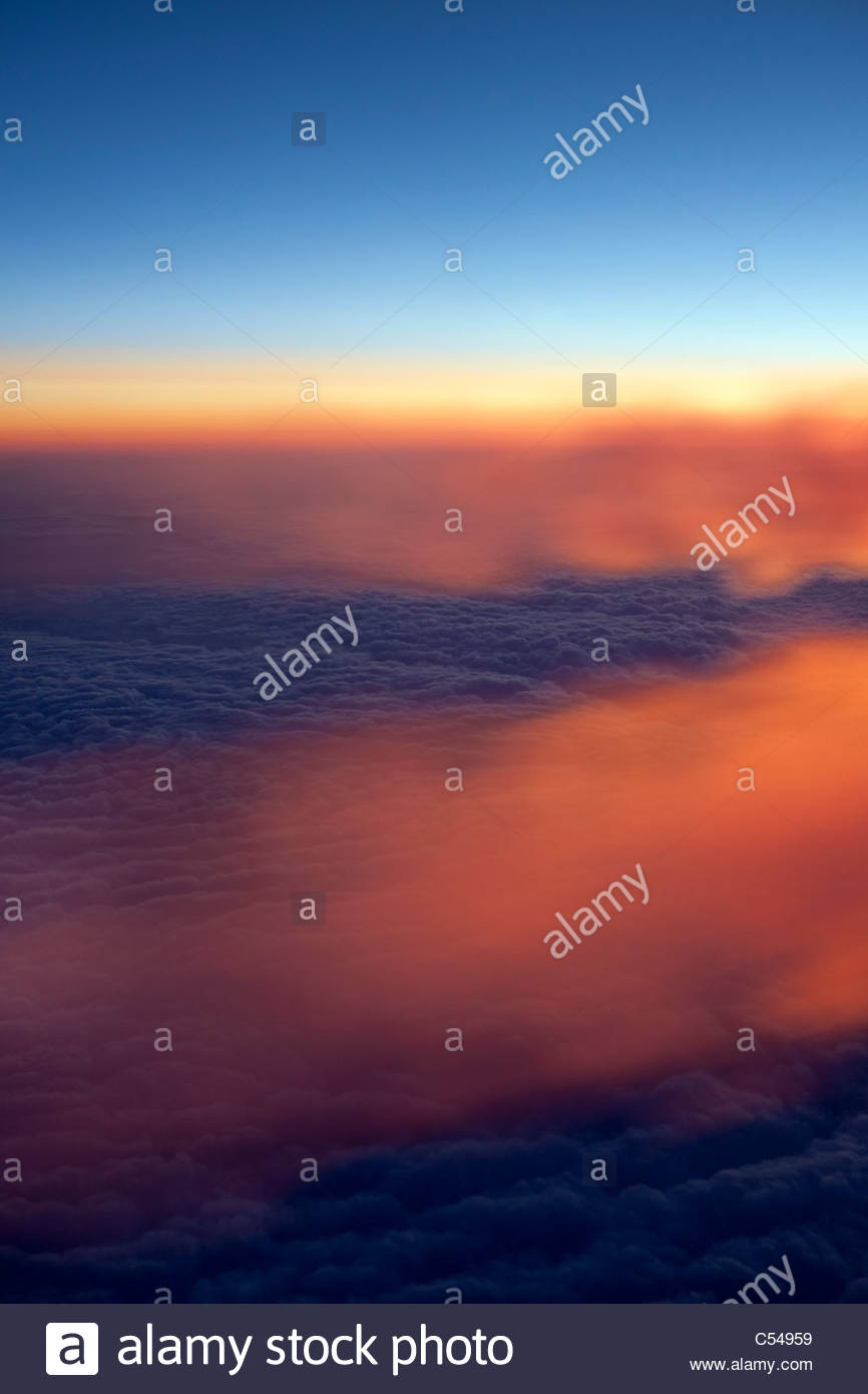 The Netherlands, Amsterdam, Aerial, Sunrise over the clouds, taken from airplane. Condensation trails, or contrails. - Stock Image