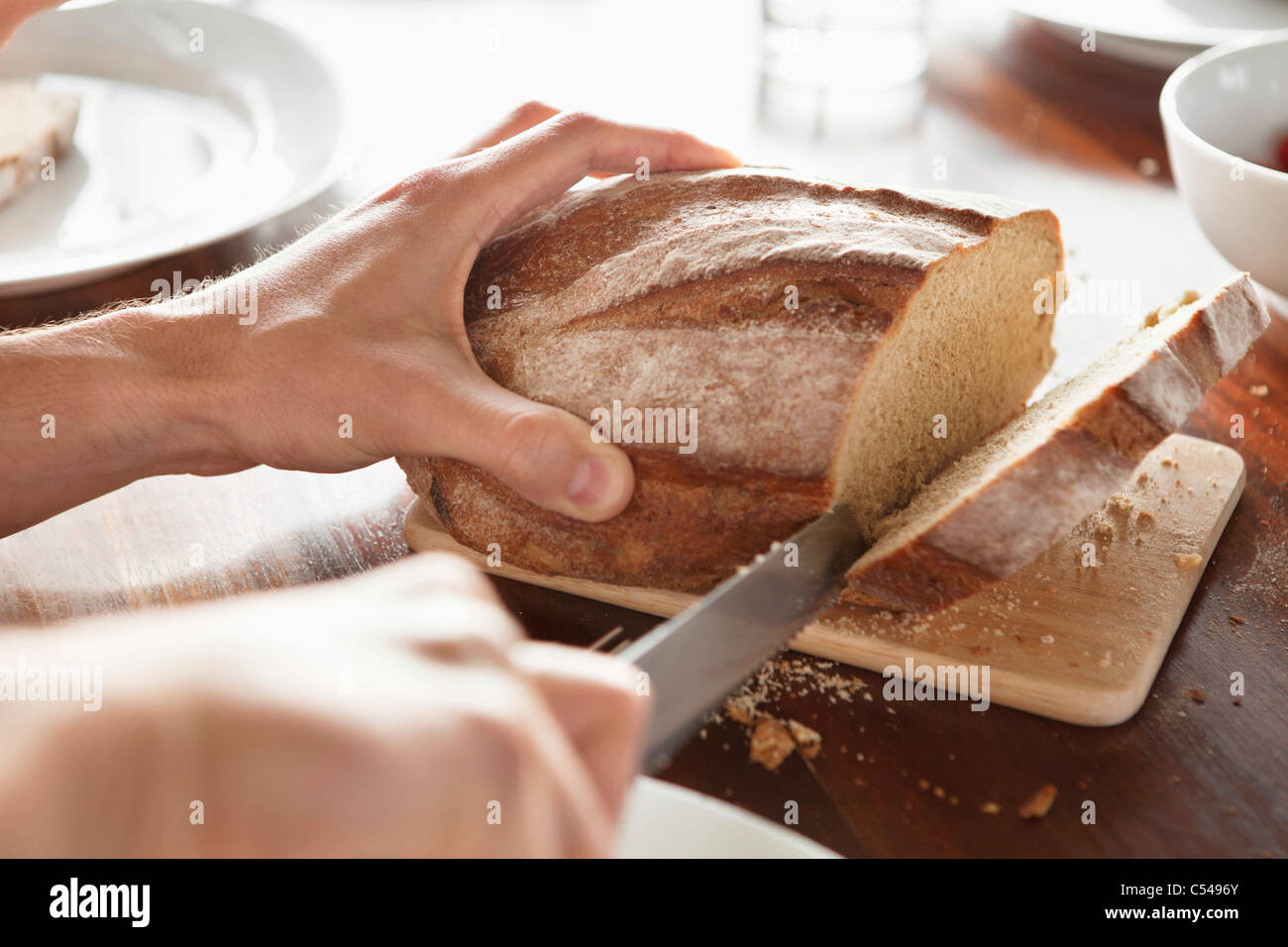Close-up of a person's hand cutting bread - Stock Image