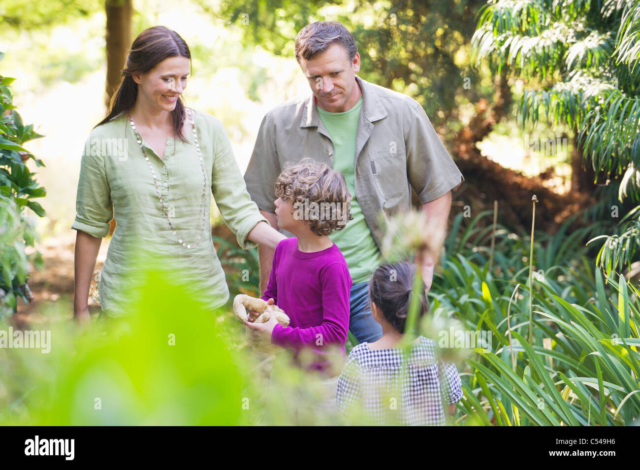 Two little children walking in a garden with their parents Stock Photo