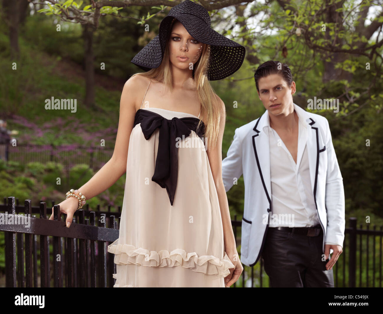 Young couple standing at a fence in a park. Springtime scenic. - Stock Image