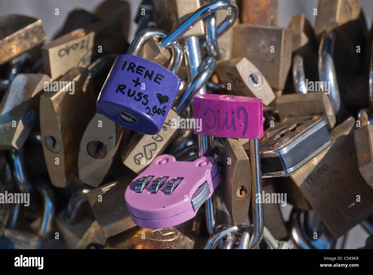Padlocks that symbolize everlasting love for a couple locked to public fence post in Florence, Italy. - Stock Image