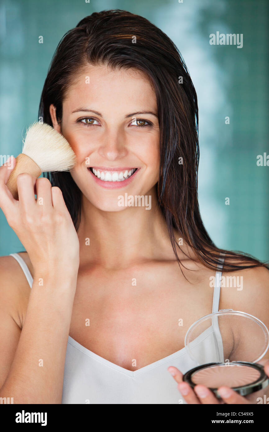 Portrait of a woman applying powder compact on her face - Stock Image
