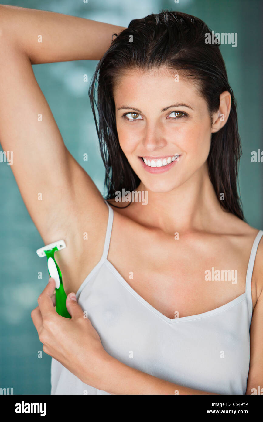 Portrait of a woman shaving her armpit - Stock Image
