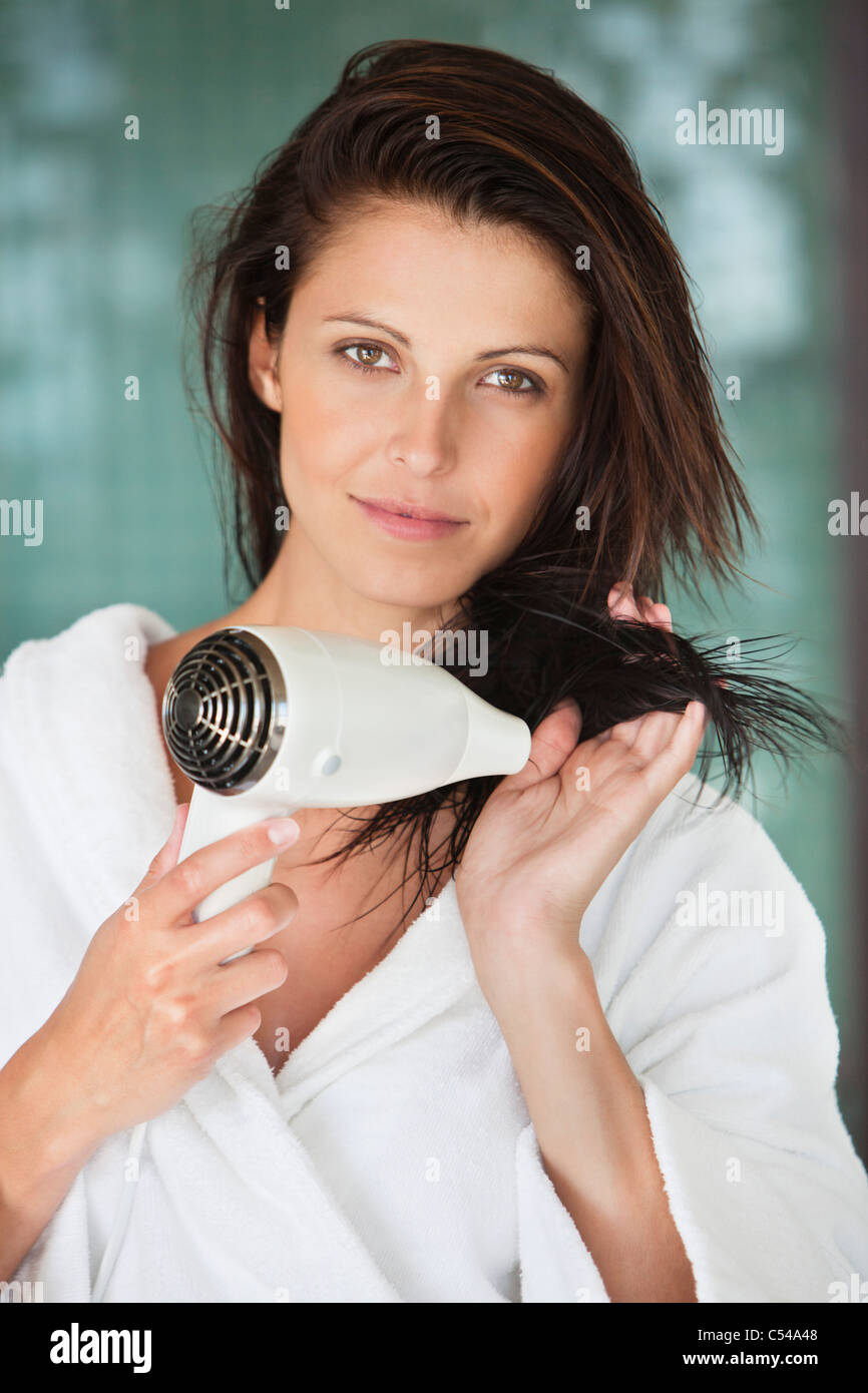 Portrait of a woman drying her hair with a hair dryer - Stock Image