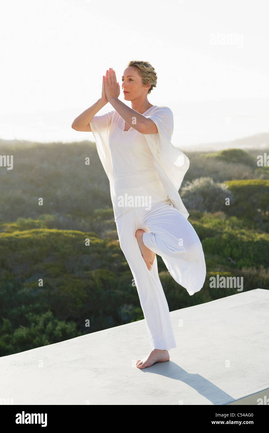 Mid adult woman practicing yoga - Stock Image