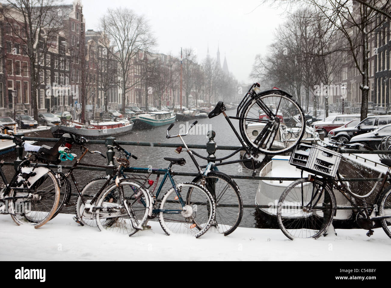 The Netherlands, Amsterdam, 17th century houses at canal called Keizersgracht. Winter, snow. Bicycles on bridge. - Stock Image