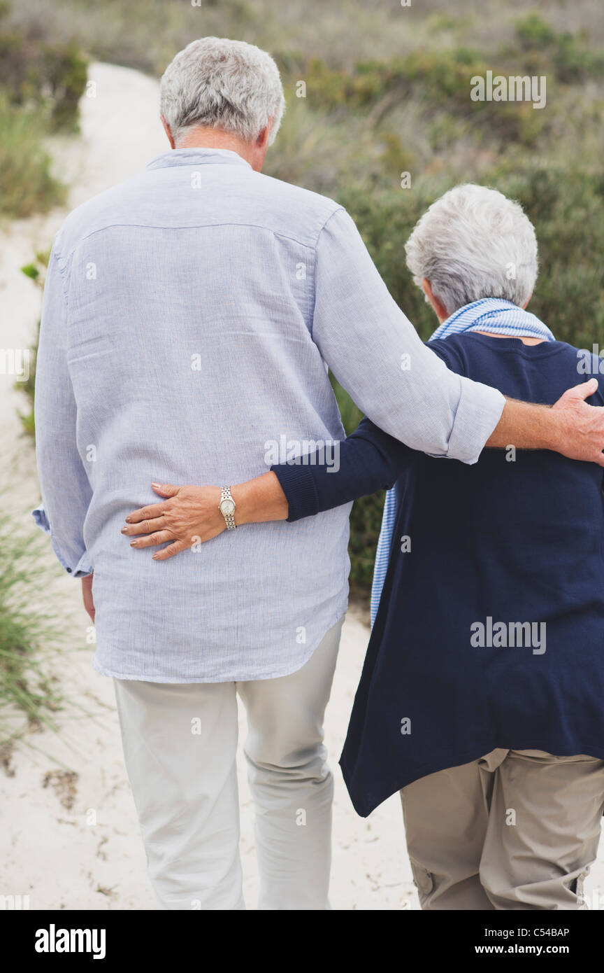 Rear view of a senior couple walking on the beach with their arms around each other - Stock Image