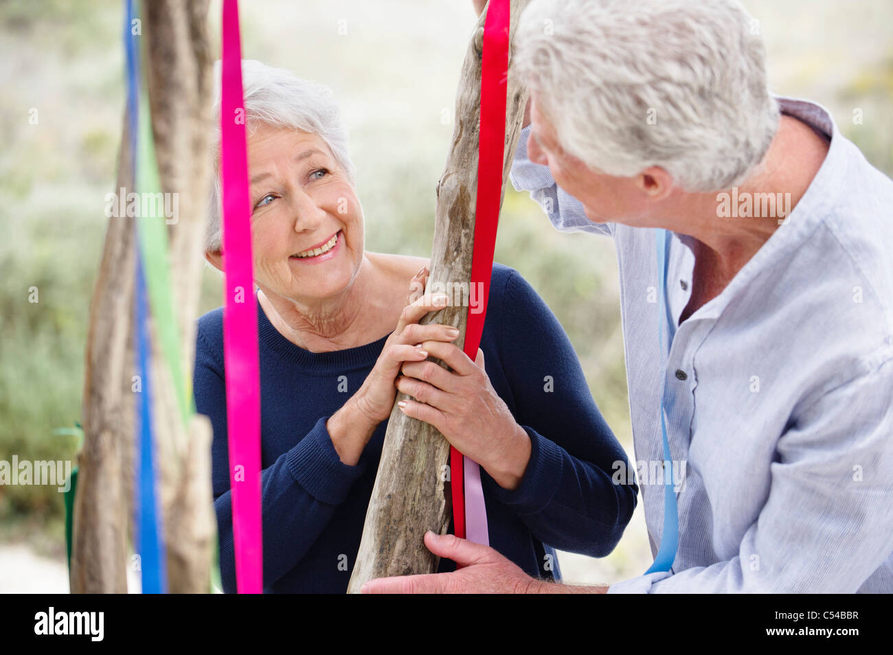 Senior couple standing near a decorated tree and smiling Stock Photo