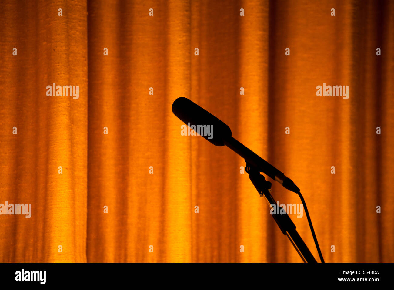 Yellow Stage Curtain and Microphone for background - Stock Image