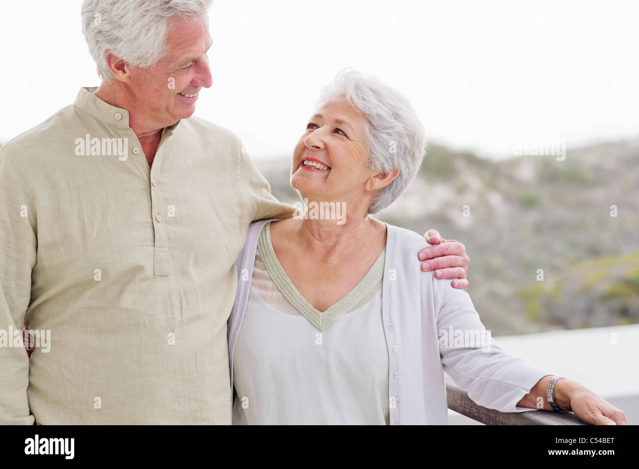Senior man standing with his arm around a senior woman - Stock Image