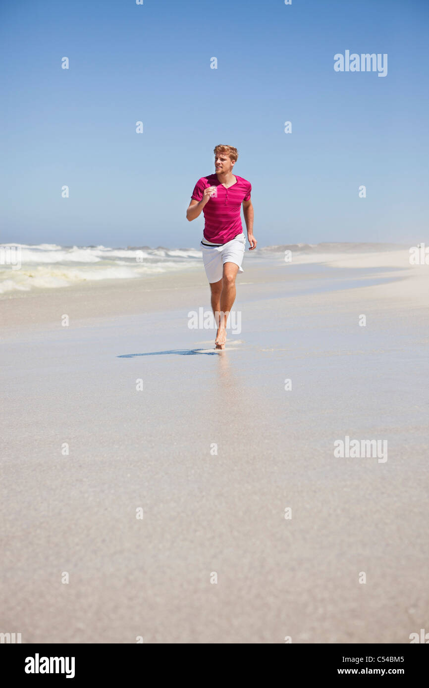 Man running on the beach Stock Photo