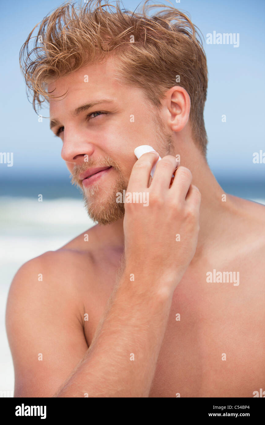 Young man applying moisturizer on his face - Stock Image
